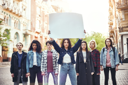 Girl power. Group of young women standing on the road during protest march. Young woman holding blank signboard over her head