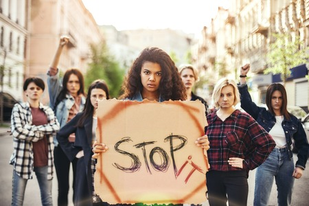 Stop War Make Peace. Young woman is holding a banner with word stop it while standing on the road during a womens march in front of female activists