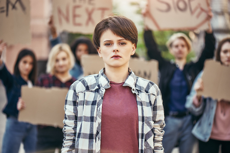 Human rights. Young woman is standing on the road during a womens march in front of female activists holding signboards.