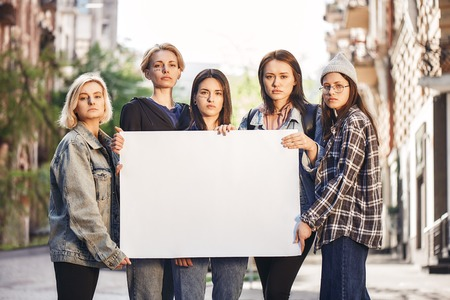 Women power. Group of young female activists are holding blank signboard while standing on the road during a womens march.