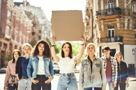 Women power. Young woman is holding blank signboard over her head while standing on the road around female activists. Stok Fotoğraf