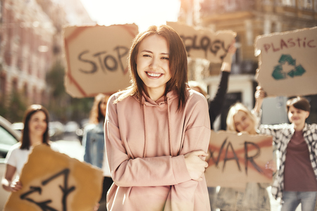 Clean your planet. Happy young woman keeping arms crossed and protesting for ecology with group of female activists while marching on the road. Stock Photo