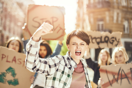 Fighting for clean earth. Young and strong woman is protesting for ecology with group of female activists while marching on the road.