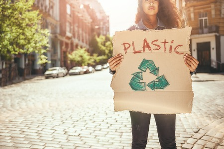 Say no to plastic. Young female activist holding a signboard with word plastic while standing on the road. Ecology concept Stock Photo