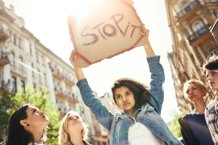 Make love not war. Strong young woman holding a signboard with word stop it over her head while standing on the road around female activists .