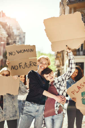 The future is female. Two happy young women are holding signboards and smiling while standing on the road around female activists.