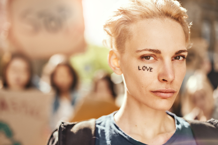 Make Love Not War. Close up photo of young blonde woman with word love written on her face standing in front of female activists on the road during protest march.