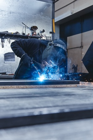 Industrial worker wearing helmet and gloves welding steel construction at the factory. Vertical shot 版權商用圖片