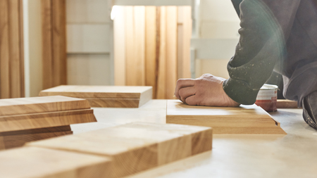 Carpenter working with wooden pieces in carpentry shop. Horizontal shot