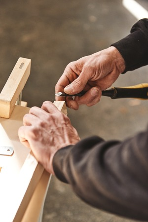Man working with a wooden plank. Woodworking and carpentry production. Furniture manufacture.
