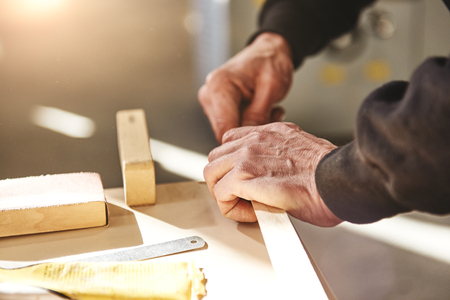Man checks the quality of a wooden plank. Woodworking and carpentry production. Furniture manufacture.
