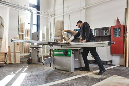 Sawing up of a wooden board on a sliding table saw. Woodworking and carpentry production. Reklamní fotografie