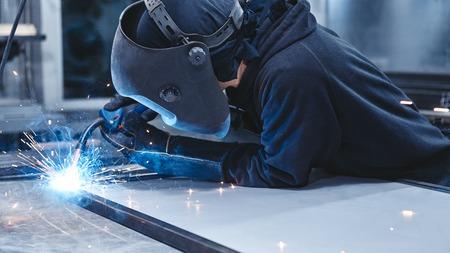 Mężczyzna pracownik nosi kask i rękawice do spawania konstrukcji stalowych w fabryce. Strzał poziomy. Ścieśniać. Widok z boku