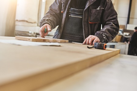 Skilled carpenter in uniform measuring a piece of wood in his woodwork workshop. Horizontal shot. Close up. Selective focus