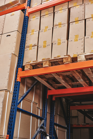 Warehouse and Logistics. The shipment pallet, stack of cardboard boxes on wooden pallet in distribution warehouse. Vertical shot