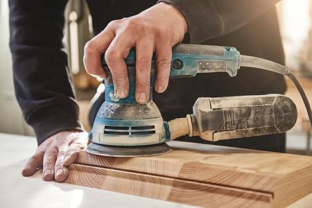 Cerca de carpintero pulido tablero de madera con una lijadora orbital en el taller. Tiro horizontal