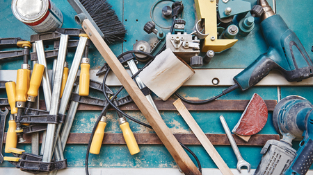 Close up of assorted tools for carpenter lying on the blue working surface. Horizontal shot
