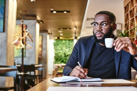 Theres no such thing as a free lunch. Portrait of a confident businessman making notes and drinking coffee while resting in the cafe