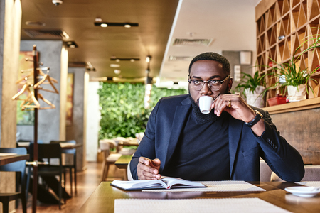 Put your thoughts in order. Portrait of a confident businessman making notes and drinking coffee while resting in the cafe Imagens