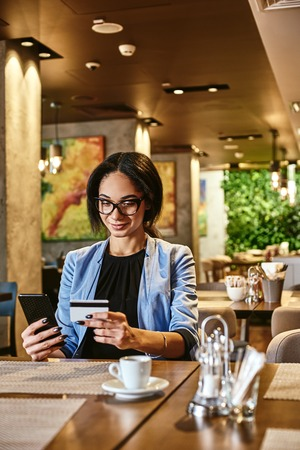 Making money is a hobby that will complement any other hobbies you have. Mixed race busy woman using credit card for shopping and paying bills on-line while sitting in coffee shop