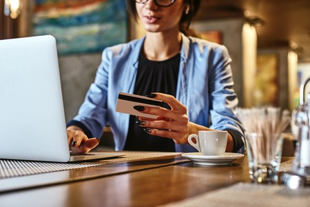 Money often costs too much. Mixed race busy woman using credit card for shopping and paying bills on-line while sitting in coffee shop 写真素材 - 124791754