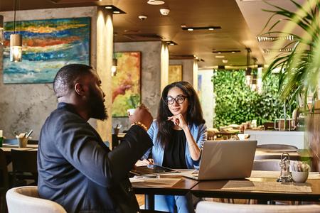 Bleiben Sie Ihrer Arbeit, Ihrem Wort und Ihrem Freund treu. Ernsthafte Frau, die während des Mittagessens im Café ihrem Kollegen zuhört