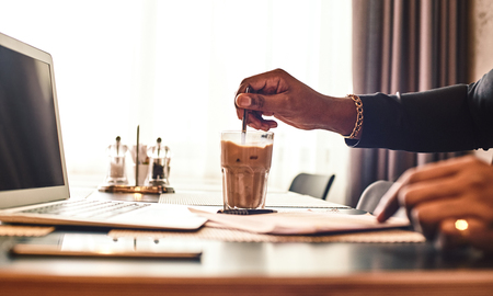 Close up of dark-skinned businessman in dark-blue jacket sitting at the table, indoors, drinking coffee. Young African entrepreneur puts sugar in his glass of coffee and mix it. Modern interior Stock Photo
