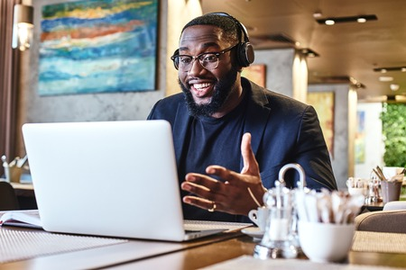 Work until you no longer need to introduce yourself. Young businessman with headphones sitting in cafe in front of laptop and networking