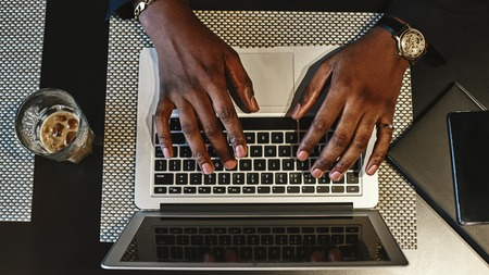 Top view of mans hands typing on a keyboard of the laptop. Imagens