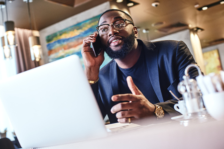 Young stylish dark-skinned businessman in a cafe talking on a cell phone Stock Photo