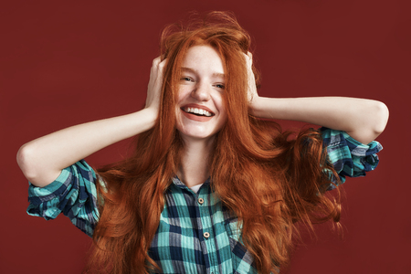 Beauty is power a smile is its sword. Close up of modern playful teenage girl touching her hair
