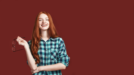 A smile is the best way to get away with trouble. Redhead girl smiling at the camera