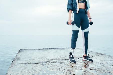 Exercising with dumbbells. Cropped image of disabled woman in sports clothing with prosthetic leg holding dumbbells while standing in front of the sea.