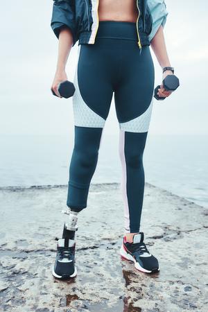 Healthy lifestyle. Vertical cropped image of sporty young disabled woman in sports clothing exercising with dumbbells while standing in front of the sea
