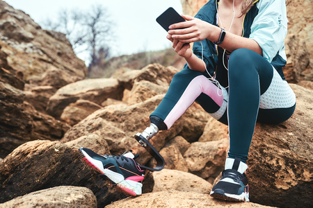 Digital technologies. Cropped image of disabled women in sport wear with leg prosthesis sitting on the boulders and holding smartphone.