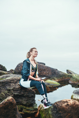 Enjoying nature and music. Happy disabled athlete woman in sportswear with prosthetic leg sitting on the stone and listening music. Stock Photo