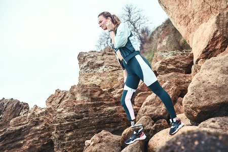 Positive disabled woman in sport wear with leg prosthesis holding phone in her hand and listening music while standing on the boulders