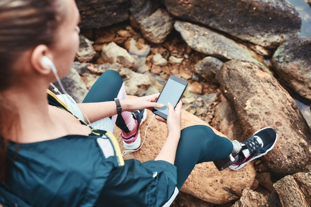 Disabled woman in sport wear with leg prosthesis holding phone in her hand and listening music while sitting on the boulders