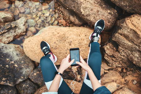 Top view of disabled woman in sport wear with leg prosthesis sitting on the boulders and holding smart phone Stock Photo