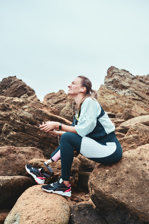 It was great workout. Happy disabled woman in sport wear with leg prosthesis sitting on the boulders, listening music and dreaming. Stock Photo