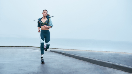 You are stronger than you think. Amazing strong disabled woman in sportswear is running outdoors near the sea Stock Photo