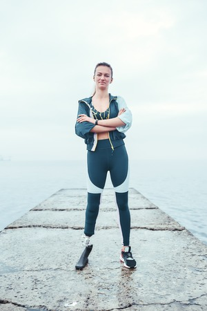 Everything depends of you. Vertical photo of confident disabled woman in sports clothing with prosthetic leg standing in front of the sea and keeping arms crossed.