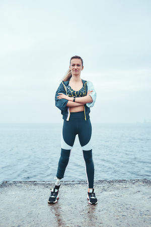 Strong and motivated. Confident disabled woman in sports clothing with prosthetic leg standing with crossed arms in front of the sea and smiling. Stock Photo