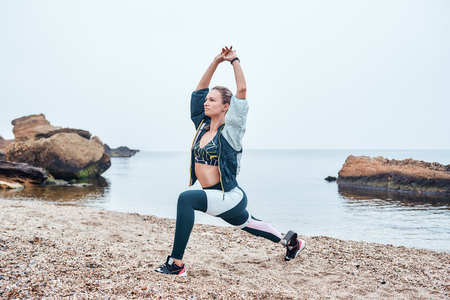Sea Inspiration. Amazing disabled athlete woman in sportswear with prosthetic leg standing in yoga pose at the beach. Imagens