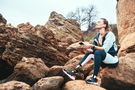 Feeling free. Happy disabled women in sport wear with leg prosthesis sitting on the boulders with closed eyes and listening music. Stock Photo
