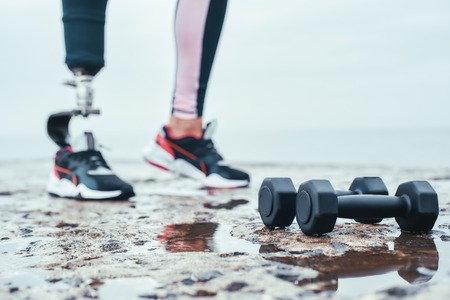 Strong and healthy. Cropped image of woman with prosthetic leg and dumbbells lying in front of the sea.
