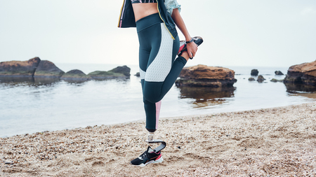 Strong body. Cropped image of disabled athlete woman in sportswear with prosthetic leg doing stretching exercises while standing at the beach