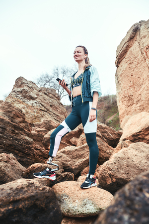 Resting after workout. Disabled woman in sport wear with leg prosthesis holding phone in her hand and listening music while standing on the boulders