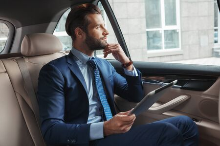 Thinking about business. Young handsome and stylish businessman in formal wear is holding digital tablet and looking in window while sitting on the back seat of his car Stok Fotoğraf