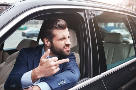 Rude businessman. Angry and rude bearded businessman in formal wear is gesturing and making a grimace while driving his car.